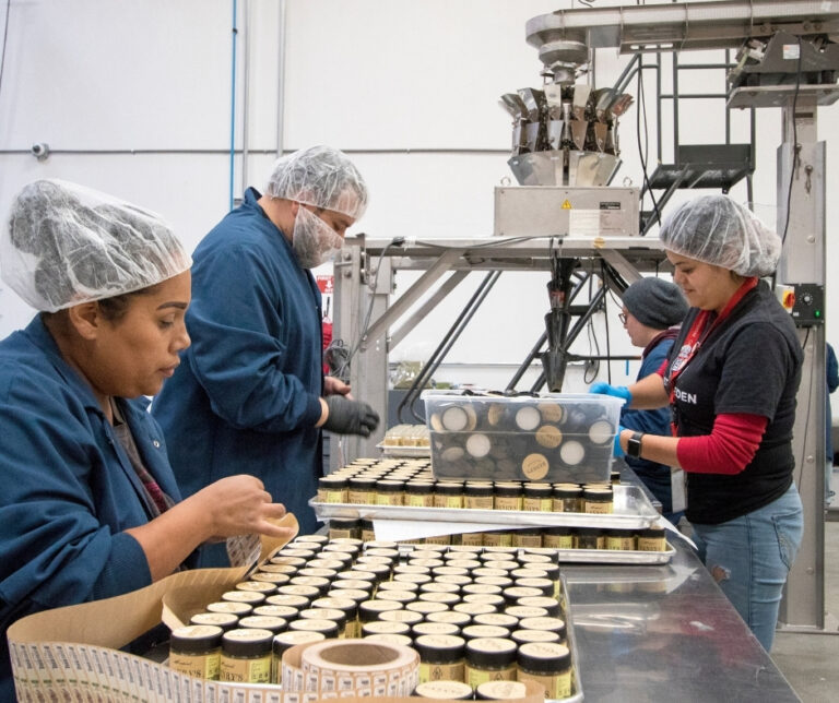 Three manufacturing employees packaging cannabis in our Work St. Center.